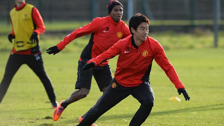Manchester United's Shinji Kagawa (R) and Ashley Young take part in a training session in Manchester, north-west England, on December 9, 2013, on the eve of their UEFA Champions League Group A match Shaktar Donetsk