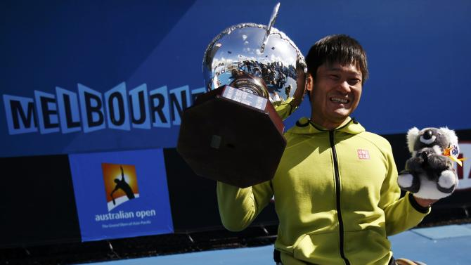 Kunieda of Japan poses with his trophy after defeating Houdet of France in their men's wheelchair singles final match at the Australian Open 2015 tennis tournament in Melbourne