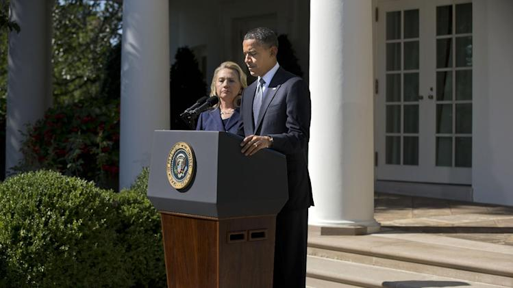 FILE - In this Wednesday, Sept. 12, 2012 file photo, Secretary of State Hillary Clinton looks on as President Barack Obama delivers a statement on the death of U.S. ambassador to Libya Christopher Stevens in the Rose Garden of the White House in Washington. Witness accounts gathered by The Associated Press give a from-the-ground perspective for the sharply partisan debate in the U.S. over the deadly incident. They corroborate the conclusion largely reached by American officials that it was a planned militant assault. But they also suggest the militants may have used a film controversy as a cover for the attack. (AP Photo/Evan Vucci)