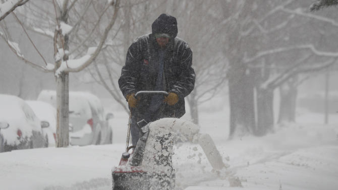 A maintenance man uses a snowblower to clear a sidewalk in Denver as a spring storm packing high winds and heavy snow swept over Colorado's Front Range and on to the eastern plains on Saturday, March 23, 2013. Forecasters predict up to a foot of snow will fall in some locations in Colorado before the storm heads toward the nation's midsection. (AP Photo/David Zalubowski)