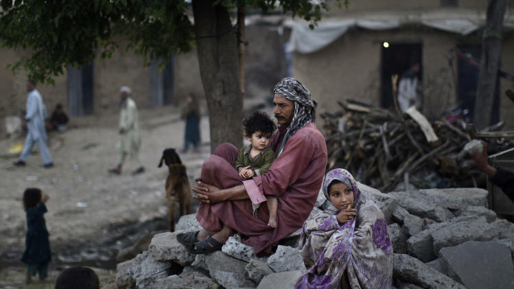 In this Thursday, April 11, 2013, photo, Pakistani daily laborer, Wakeel Mohammed, 38, who fled Pakistan's tribal region, due to fighting between the Taliban and the army, and took refuge in Islamabad, sits on a roadside with his daughter Halimah, 1, sitting on his lap and his relative Khadijah, 7, right, near their home, in a poor neighborhood on the outskirts of Islamabad, Pakistan. Moderate politicians from some of Pakistan's most violent areas are defying the threat of violence to run in upcoming nationwide elections, but they're increasingly turning to social media and phone calls that allow them to campaign from a distance. (AP Photo/Muhammed Muheisen)