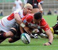 Tonga&#39;s scrum-half Taniela Moa (L) tackles Japan&#39;s centre Ryan Nicholas during their match at the Pacific Nations Cup rugby union tournament in Tokyo. Tonga defeated Japan 24-20