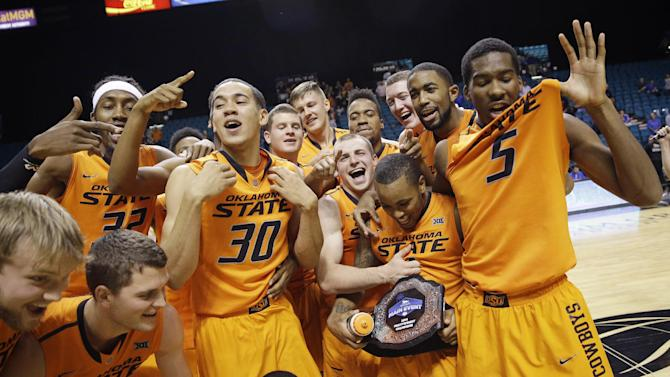 Oklahoma State players celebrate as they pose for photographers after defeating Tulsa 73-58 in an NCAA college basketball game Wednesday, Nov. 26, 2014, in Las Vegas, to win the MGM Grand Main Event tournament. (AP Photo/John Locher)