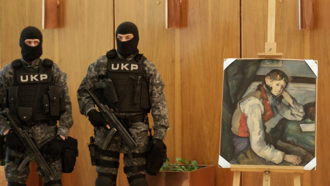 "Members of Serbian police guard the stolen ""The Boy in the Red Vest"" painting by French impressionist Paul Cezanne, in Belgrade, Serbia, Thursday, April 12, 2012. Serbian police arrested three people overnight in connection with the robbery of the art work. They said police raids and the arrests in the capital of Belgrade and in the central city of Cacak were conducted in coordination with police from several European countries. (AP Photo/Darko Vojinovic)"