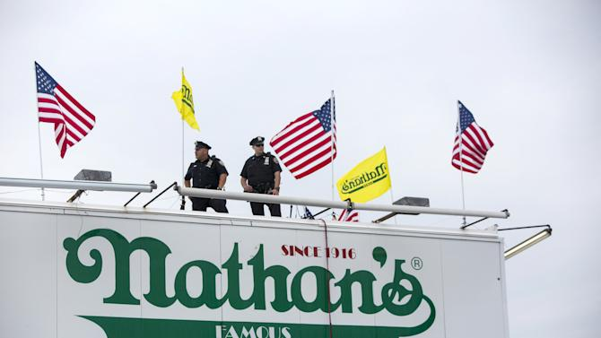 New York Police Officers stand guard on a rooftop during the annual Fourth of July 2015 Nathan's Famous Hot Dog Eating Contest in Brooklyn, New York