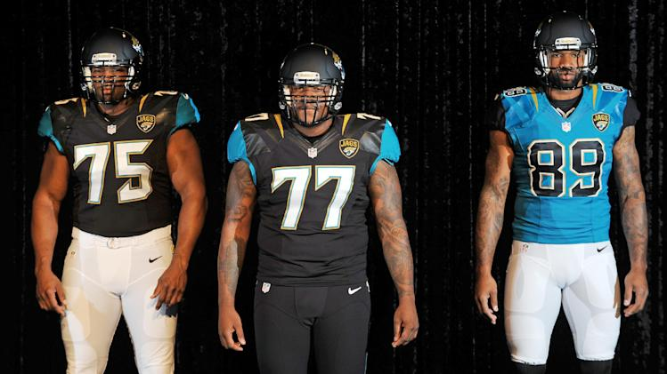 Jacksonville Jaguars players Eugene Monroe, left,  Uche Nwaneri, center,  and Marcedes Lewis, right, model variants of the Jacksonville Jaguars new uniforms during their reveal.  The Jacksonville Jaguars previewed the team's new Nike designed uniforms Tuesday afternoon in the West Touchdown  Club at EverBank Field, April 23, 2013.  (AP Photo/The Florida Times-Union, Bob Self)