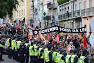 <p>Demonstrators take part in a protest against the Portuguese government's 2013 austerity budget, near the Parliament in Lisbon. The Portuguese parliament adopted on Wednesday a 2013 austerity budget that includes draconian tax increases required by international creditors, in the teeth of swelling street protests.</p>