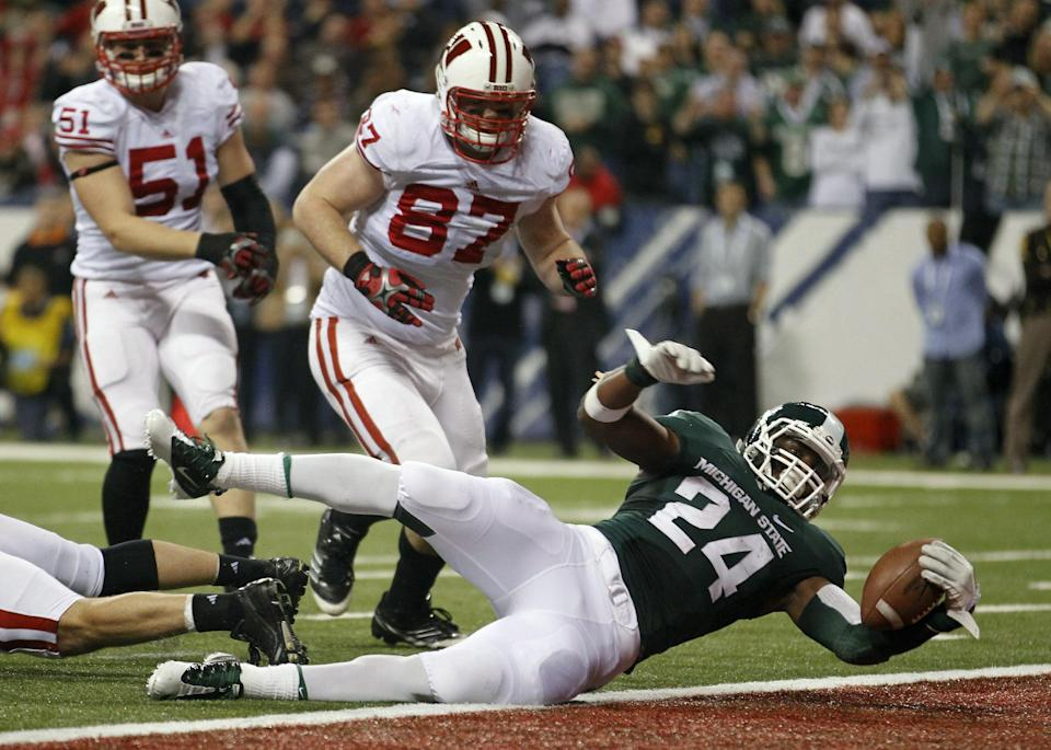 Michigan State's Le'Veon Bell goes in to the end zone for a touchdown ahead of Wisconsin's Ethan Hemer during the first half of the Big Ten conference championship NCAA college football game on Saturday, Dec. 3, 2011 in Indianapolis. (AP Photo/Michael Conroy)