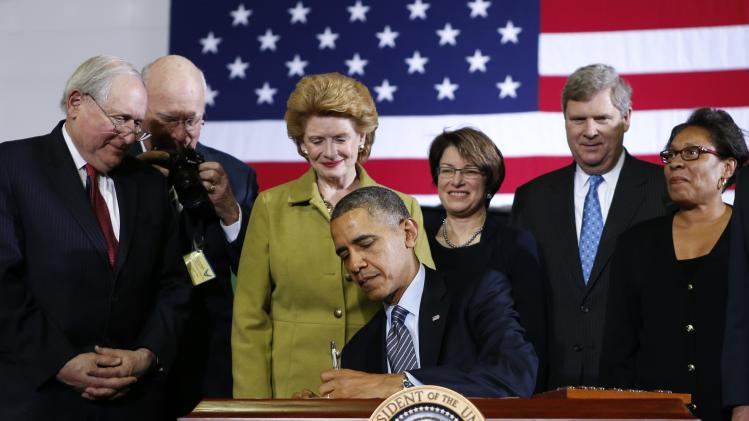 President Barack Obama signs the farm bill into law at Michigan