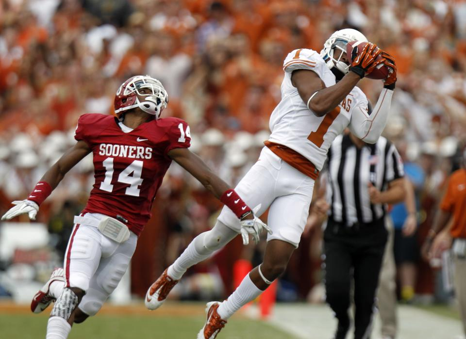 Texas wide receiver Mike Davis (1) catches a pass in front of Oklahoma defensive back Aaron Colvin (14)  during the first half of an NCAA college football game at the Cotton Bowl Saturday, Oct. 13, 2012, in Dallas. (AP Photo/LM Otero)