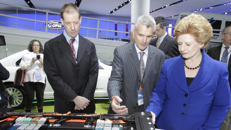 Ford Chief Technical Officer Paul Mascarenas, center, shows off the automaker's electric car battery to Sen. Debbie Stabenow and Ron Bloom, President Obama's Senior Counselor for Manufacturing Policy at the North American International Auto Show in Detroit, Tuesday, Jan. 11, 2011. (AP Photo/Carlos Osorio)
