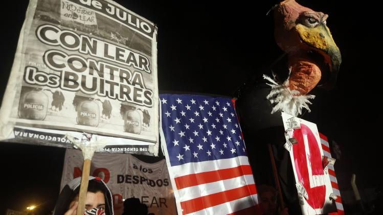 "A protester, rallying against layoffs holds a placard that reads ""With Lear against the vultures"" next to a mock vulture, in front of the factory of U.S. automotive supplier Lear on the outskirts of Buenos Aires"