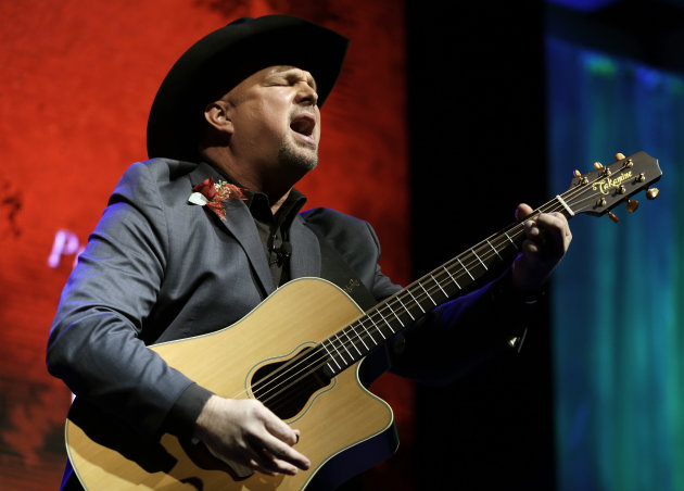 "FILE - This Oct. 7, 2012 photo shows Garth Brooks singing ""Papa Loved Mama,"" a song written by Kim Williams, as Williams is inducted into the Nashville Songwriters Hall of Fame in Nashville, Tenn. On Sunday, Oct. 21, Brooks will be inducted into the Country Music Hall of Fame. (AP Photo/Mark Humphrey, file)"