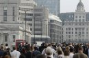 Commuters walk to work across London Bridge, heading into the City of London