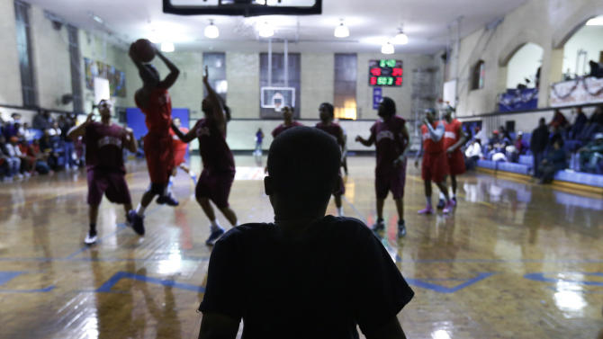 In this Monday, Dec. 17, 2012 photo, a young boy is silhouetted as he watches a basketball tournament for reputed gang members and associates at the St. Sabina Catholic Church in the Auburn-Gresham neighborhood on Chicago's South Side. The 12-week basketball league is aimed at cooling gang hostilities. (AP Photo/Charles Rex Arbogast)
