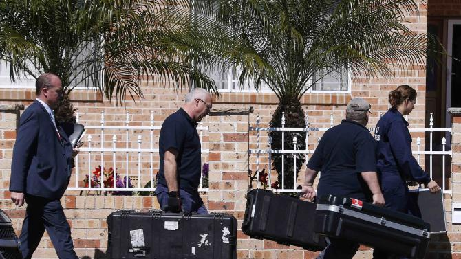 Members of the Australian Federal Police forensic unit carry equipment into a house that was involved in pre-dawn raids in the western Sydney suburb of Guilford