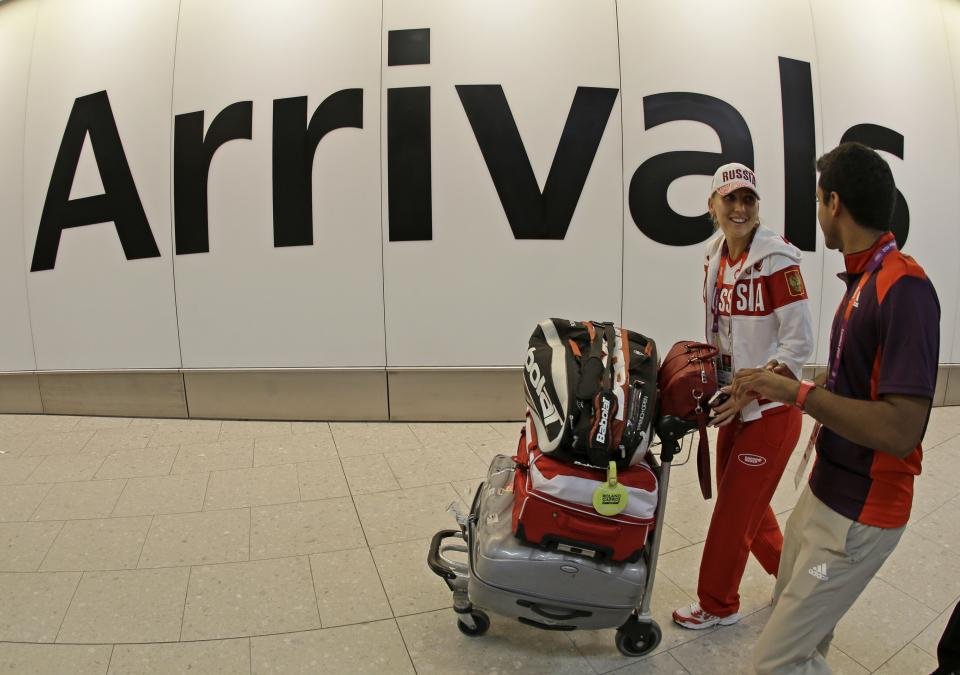 Russian tennis player Elena Vesnina talks with an Olympic volunteer after arriving at Heathrow Airport Wednesday, July 18, 2012 as London prepares for the 2012 Summer Olympics. (AP Photo/Charlie Riedel)
