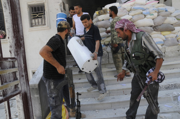 In this Tuesday, July 31, 2012 photo, Free Syrian Army soldiers loot a police station in Aleppo, Syria. (AP Photo/Alberto Prieto)