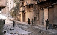 Syrian government forces walk past rubble along a street in the northern city of Aleppo during fighting against rebel forces, september 24, 2012. The emir of Qatar has called for an Arab intervention in Syria and a no-fly zone to protect refugees as President Bashar al-Assad's forces stepped up the battle for Aleppo