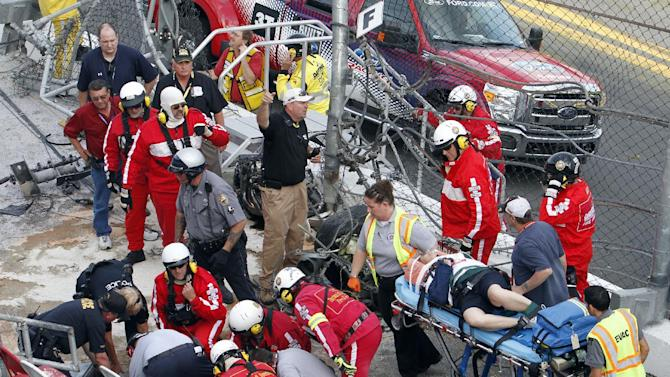 Injured spectators are treated after a crash at the conclusion of the NASCAR Nationwide Series auto race Saturday, Feb. 23, 2013, at Daytona International Speedway in Daytona Beach, Fla. Driver Kyle Larson's car hit the safety fence sending car parts and other debris flying into the stands. (AP Photo/David Graham)