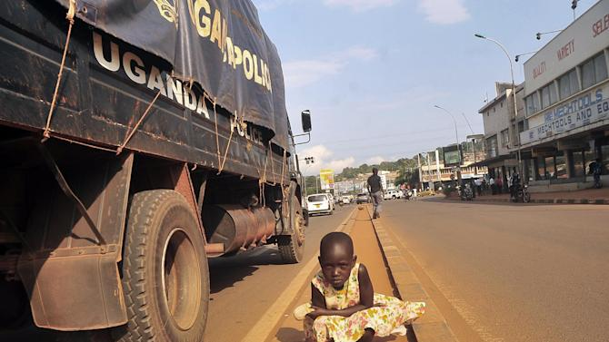 "A Ugandan street child poses in the middle of the streets as a police truck goes past her, in Kampala, Uganda, Thursday,July 17, 2014. Homeless children in Uganda's urban centers face beatings and abuse at the hands of police and local officials, Human Rights Watch charged in a new report that urges Ugandan authorities to protect street children from targeted roundups and arbitrary detentions. A police spokesman said the allegations are ""totally not true."" (AP Photo / Stephen Wandera)"