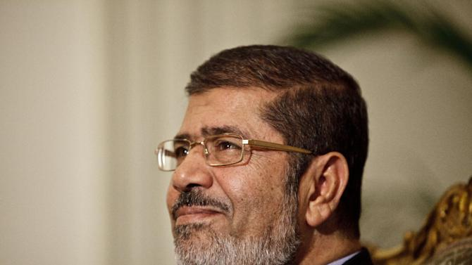 "Egyptian President Mohammed Morsi is seen during a photo opportunity in his office at the presidential palace in Cairo, Egypt, Saturday, Dec. 8, 2012.  Egypt's military said Saturday that serious dialogue is the ""best and only"" way to overcome the nation's deepening conflict over a disputed draft constitution hurriedly adopted by Islamist allies of President Mohammed Morsi, and recent decrees granting himself near-absolute powers.(AP Photo/Maya Alleruzzo)"
