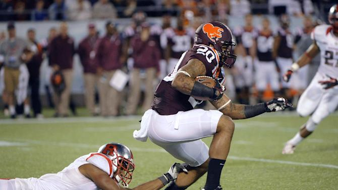 Virginia Tech's Michael Holmes (20) slips a tackle by Rutgers' Logan Ryan (11) during a kick return in the first quarter of the Russell Athletic Bowl NCAA college football game on Friday, Dec. 28, 2012, in Orlando, Fla. (AP Photo/Brian Blanco)