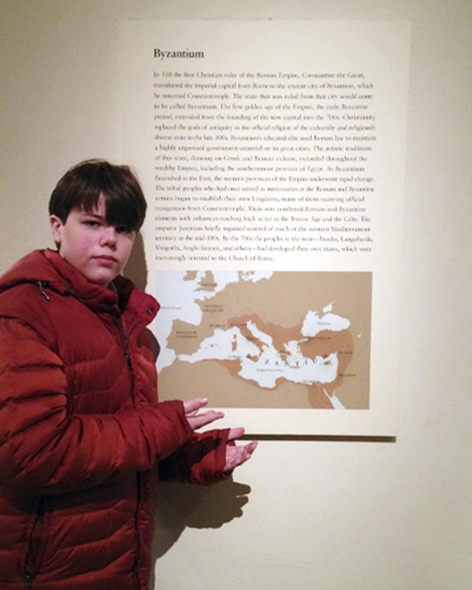 This February 2012 photo provided by Joanne Lerman shows her son Benjamin Lerman, of West Hartford, Conn., posing by a map at the Metropolitan Museum of Art in New York.  Benjamin pointed out inaccurate boundaries on the map, which a curator at the museum subsequently confirmed. (AP Photo/Joanne Lerman)