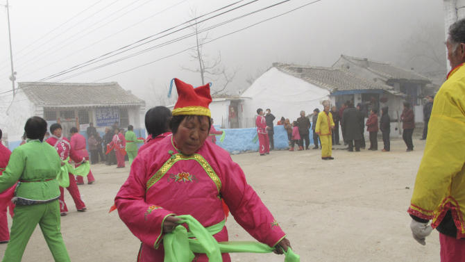 In this photo taken Monday, Feb. 25, 2013, farmers perform a dance as part of local Spring Festival celebrations in Luotuowan village in northern China's Hebei province. New Chinese leader Xi Jinping visited the village in December 2012 as part of efforts to style himself as a no-frills man-of-the-people. Xi has also presented himself as an economic reformer and an iron-fisted graft-buster, spurring expectations for change, but as he prepares to be appointed president, pressure will be growing on him to deliver. (AP Photo/Gillian Wong)
