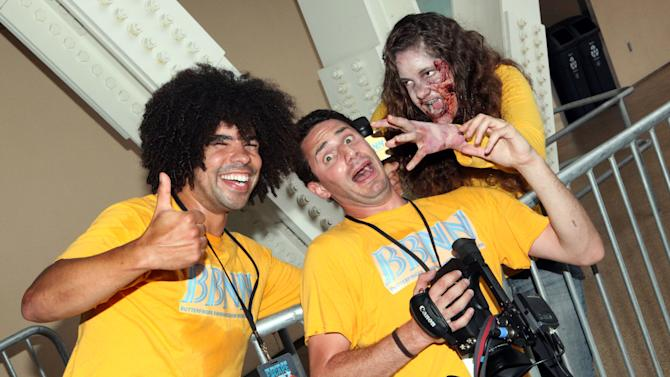 """COMMERCIAL IMAGE - In this image provided by Butterfinger, Butterfinger Barmageddon News Network reporters find end-of-world evidence of zombies inside """"The Walking Dead Escape"""" event at Comic-Con on Thursday, July 12, 2012 in San Diego, Calif. (Photo by Casey Rodgers/Invision for Butterfinger)"""