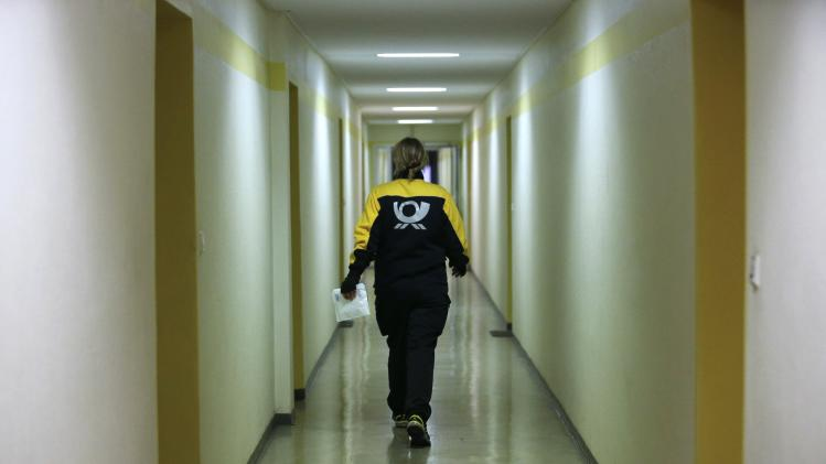 Postwoman Standke of the German postal and logistics group Deutsche Post walks inside a building during her delivery tour in Berlin's Mitte district