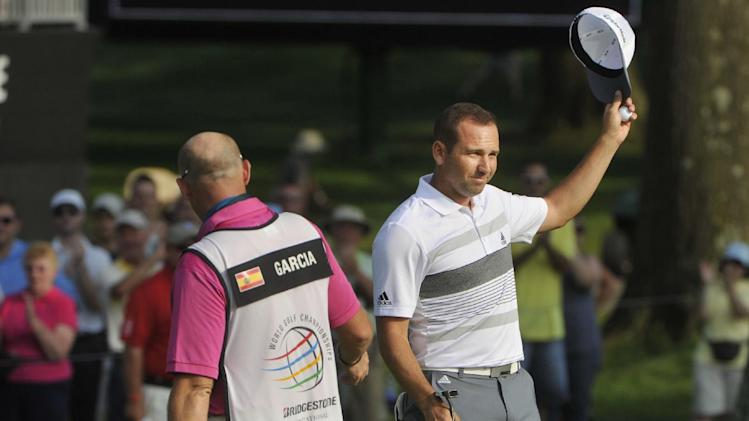 Sergio Garcia of Spain waves to the crowd after making a birdie at the 18th hole, during the second round of the Bridgestone Invitational golf tournament, Friday Aug. 1, 2014, in Akron, Ohio. Garcia shot a 61 for the day. With Garcia is his caddy Neil Wallace. (AP Photo/Phil Long)