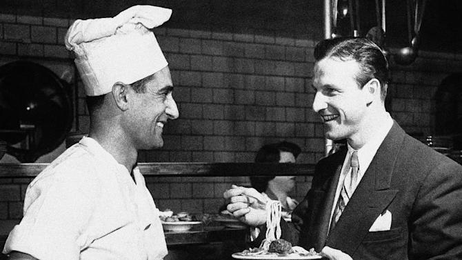 FILE- In this Feb. 18, 1951, file photo, Stan Musial eats spaghetti and talks to Chef Marie Ravetta in the kitchen of Stan Musial and Biggies restaurant in St. Louis, shortly after Musial signed his 1951 contract with the St. Louis Cardinals. Musial, one of baseball's greatest hitters and a Hall of Famer with the Cardinals for more than two decades, has died. He was 92. Stan the Man won seven National League batting titles, was a three-time MVP and helped the Cardinals capture three World Series championships in the 1940s. The Cardinals announced Musial's death in a news release. They said he died Saturday evening, Jan. 19, 2013, at his home surrounded by family. (AP Photo/File)
