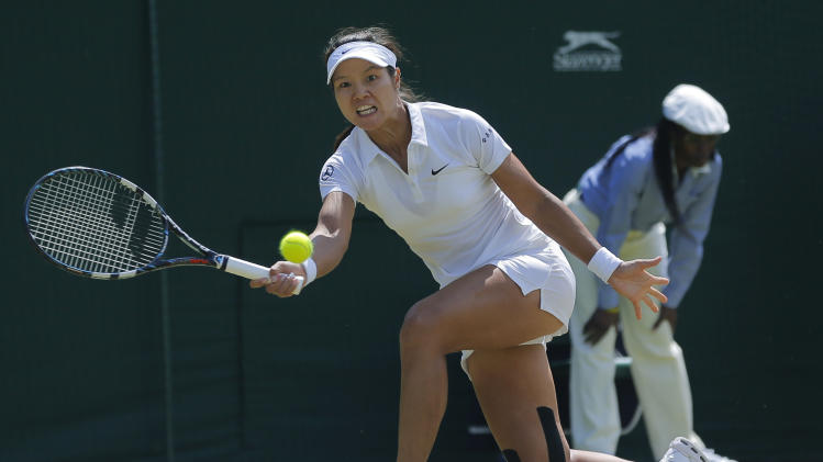 "FILE - In this June 27, 2014 file photo, Li Na of China plays a return to Barbora Zahlavova Strycova of the Czech Republic during their women's singles match at the All England Lawn Tennis Championships in Wimbledon, London. Li is pulling out of the U.S. Open because of a knee injury. Li says Thursday, July 31, 2014, in a posting on Facebook that she has ""been struggling"" with her knee since March ""and it is just not where I need it to be in order to play at the highest level.""(AP Photo/Pavel Golovkin, File)"