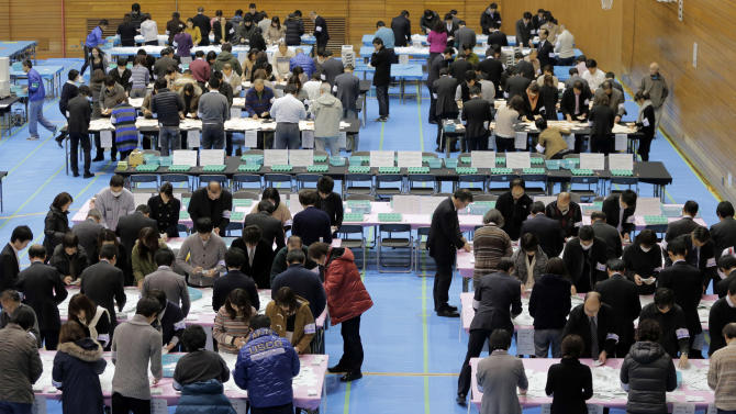 Election workers count votes at a ballot counting center in Tokyo, Sunday, Dec. 16, 2012. The main opposition Liberal Democratic Party won a clear majority in Japanese parliamentary elections Sunday, media exit polls showed, signaling a rightward shift in the government that could further heighten tensions with rival China. (AP Photo/Itsuo Inouye)