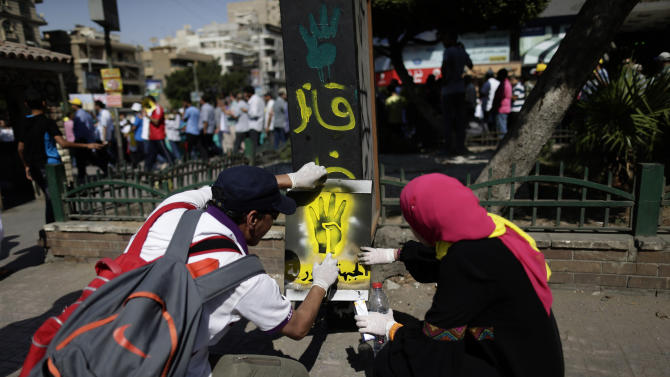 """FILE - In this file photo taken Friday, Sept. 13, 2013, supporters of Egypt's ousted President Mohammed Morsi paint graffiti with a spray against Egyptian Defense Minister Gen. Abdel-Fattah el-Sissi and four raised fingers, which has become a symbol of the Rabaah al-Adawiya mosque, where Morsi supporters had held a sit-in for weeks that was violently dispersed in August, as others march, background, during a protest in Cairo, Egypt. The Arabic reads, """"Killer."""" A heavy crackdown has thrown the 85-year-old Brotherhood into an existential crisis. Once Egypt's dominant political force, it is now reduced to keeping a campaign of street protest simmering to show it cannot be completely wiped out and must one day have a place again in the political system. (AP Photo/Hassan Ammar, File)"""
