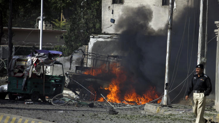 Pakistani police officer walks past burning vehicle at the site of suicide bombing in Quetta, Pakistan, Wednesday, Sept. 7, 2011. A pair of suicide bombers attacked the house of a top military officer in the southwestern city of Quetta, killing his wife and scores of other people, including soldiers, authorities said. (AP Photo/Arshad Butt)
