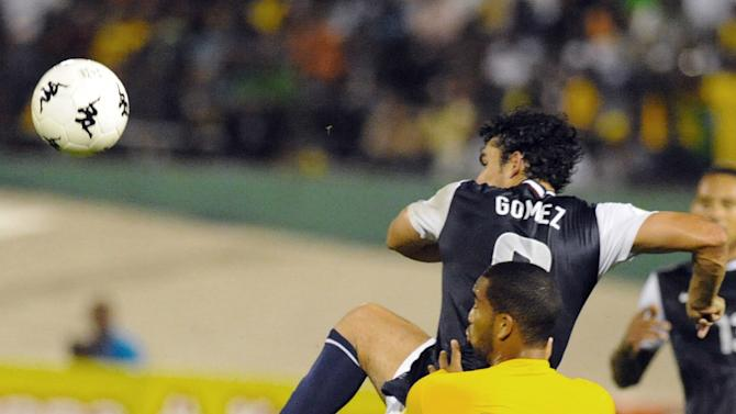 United States' Herculez Gomez, rear, fights for the ball with Jamaica's Adrian Mariappa during a 2014 World Cup qualifying soccer match in Kingston, Jamaica, Friday, Sept. 7, 2012. (AP Photo/Collin Reid)