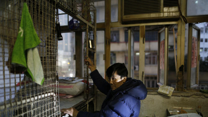 In this Jan. 25, 2013 photo, 62-year-old Cheng Man Wai climbs up to the 1.5 square meter (16 square feet) cage he calls home, in Hong Kong. For many of the richest people in Hong Kong, one of Asia's wealthiest cities, home is a mansion with an expansive view from the heights of Victoria Peak. For some of the poorest, home is a metal cage. Some 100,000 people in the former British colony live in what's known as inadequate housing, according to the Society for Community Organization, a social welfare group.  (AP Photo/Vincent Yu)