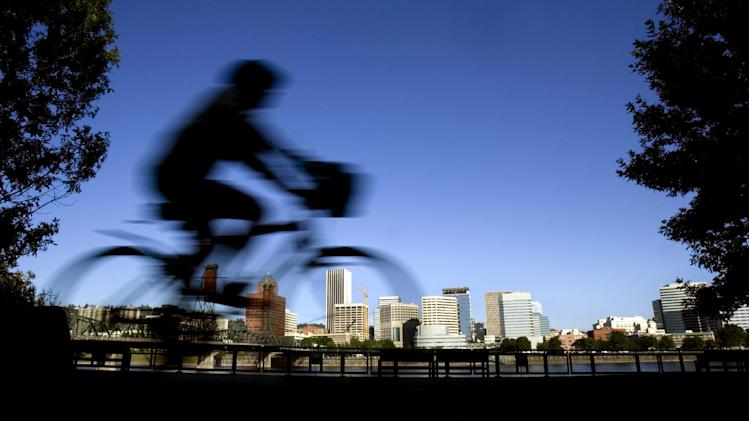 FILE-  In this July 10, 2008 file photo, a bicyclist is a blur traveling along the east bank of the Willamette River as the downtown skyline is bathed in early morning sunlight in Portland, Ore. Researchers at Portland State University found that the Portland atmosphere and culture is a magnet for the young and college educated, even though a disproportionate share of them are working in part-time jobs or positions that don't require a college degree. (AP Photo/Don Ryan, File)