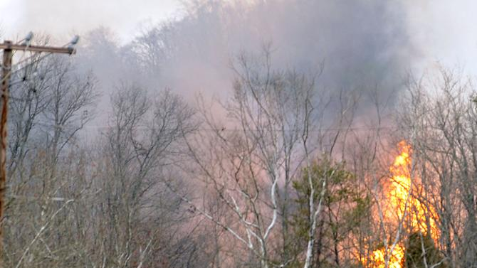 Flames burn from a gas line explosion near Sissonville, W.Va., Tuesday, December 11, 2012. At least five homes went up in flames Tuesday afternoon and a badly damaged section of Interstate 77 was shut down in both directions near Sissonville after a natural gas explosion triggered an hour-long inferno that officials say spanned about a quarter-mile.  (AP Photo/The Charleston Gazette, Rusty Marks)