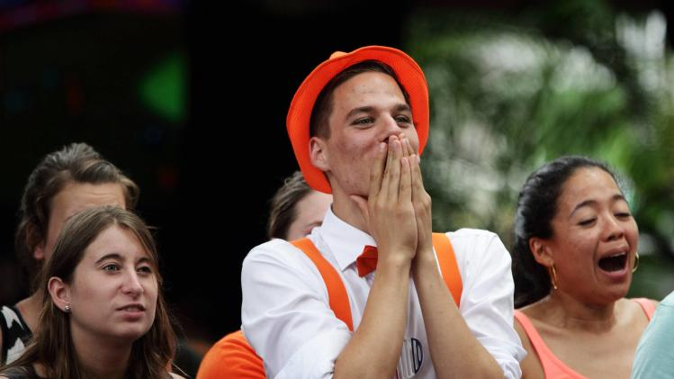 Fans supporting the Netherlands react after defeating Mexico 2-1 in a knockout match in the 2014 World Cup round of 16 game during, a public viewing area in Paramaribo