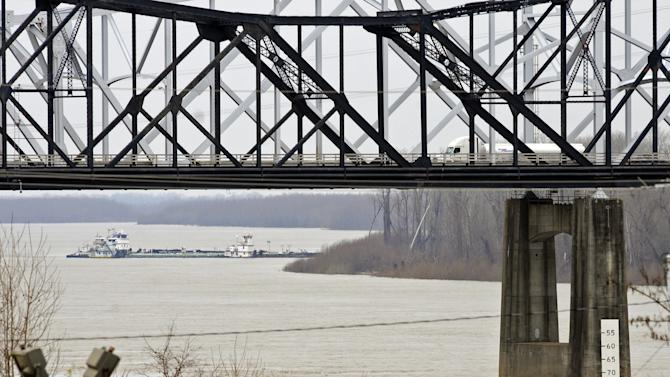 CORRECTS DATE TO JAN. 28, NOT JAN. 18 - The towboat Natures Way Endeavor banks a barge against the western bank of the Mississippi River, Monday, Jan. 28, 2013 as an 18-wheeler crosses the Interstate 20 bridge. Cleanup crews with booms skimmed oily water from the Mississippi River Monday, a day after a barge with more than 80,000 gallons of oil struck a railroad bridge near Vicksburg, spreading a sheen of light crude that kept part of the waterway shut to ship traffic Monday, authorities said. (AP Photo/Eli Baylis)