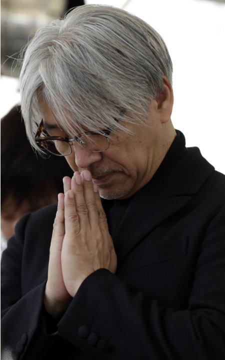 Japanese musician Sakamoto takes part in a moment of silence during a rally in Tokyo, to mark the second-year anniversary of the March 11, 2011 earthquake and tsunami