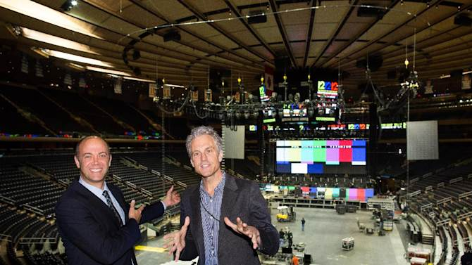 """Producers David Saltzman, left, and John Sykes speak to the media and pose for photographs as workers prepare Madison Square Garden for the """"12-12-12"""" concert whose proceeds will aid the victims of Superstorm Sandy, Tuesday, Dec. 11, 2012, in New York. The Dec. 12 concert will feature artists Bon Jovi, Eric Clapton, Dave Grohl, Billy Joel, Alicia Keys, Chris Martin, The Rolling Stones, Bruce Springsteen & the E Street Band, Eddie Vedder, Roger Waters, Kanye West, The Who and Paul McCartney. (AP Photo/John Minchillo)"""