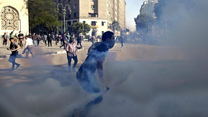 Egyptian protesters clash with security forces near Tahrir square, in Cairo, Egypt, Wednesday, Nov. 28, 2012. Egyptian state television says the country's highest appeal court has decided to suspend its work nationwide to protest the president's decrees giving himself nearly absolute powers. (AP Photo/ Khalil Hamra)