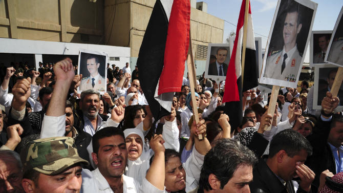 In this photo released by the Syrian official news agency SANA, medical staff members along with relatives of fifteen killed soldiers and security force members, hold pictures of Syrian President Bashar Assad and his father late President Hafez Assad as they watch the military police carry the coffins into ambulances before sending the bodies to their hometowns for burial, at a military hospital in Damascus, Syria, Tuesday, April 26, 2011. The agency did not report the circumstances of their deaths but they are believed to have been victims of the ongoing civil unrest against the government. (AP Photo/SANA) EDITORIAL USE ONLY
