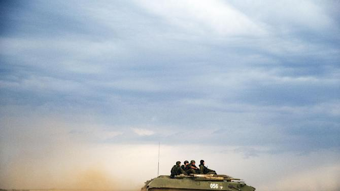 A Russian APC moves in a field in about 10 kilometers (6.2 miles) from the Russia-Ukrainian border control point at Russian town of Donetsk, Rostov-on-Don region, Monday, Aug. 18, 2014. (AP Photo/Pavel Golovkin)