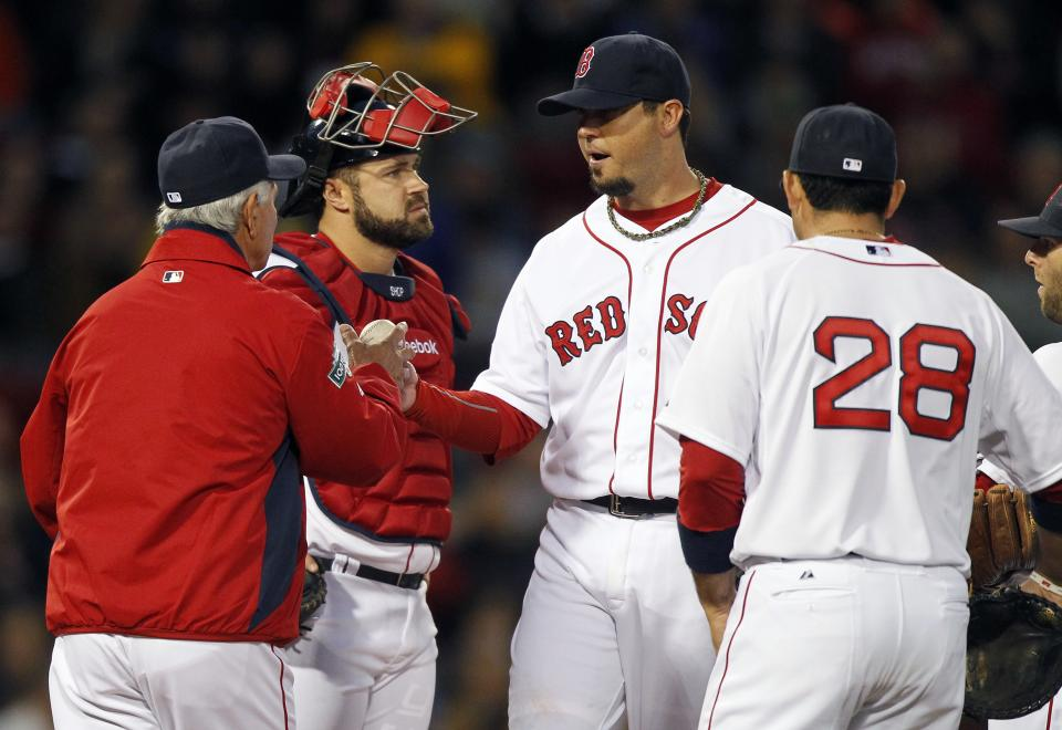 Boston Red Sox pitcher Josh Beckett, second from right, hands the ball to manager Bobby Valentine, left, and leaves the game as catcher Kelly Shoppach, second from left, and Adrian Gonzalez (28) watch in the third inning of a baseball game against the Cleveland Indians in Boston, Thursday, May 10, 2012. (AP Photo/Michael Dwyer