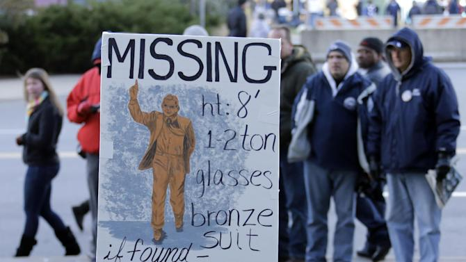 In this Nov. 23, 2013 file photo, college football fans pause at the sight outside Beaver Stadium where there once stood a bronze statue of long-time Penn State football coach Joe Paterno before an NCAA college football game between Penn State and Nebraska in State College, Pa. The Nittany Lions have had two years of modified success under coach Bill O'Brien, and as the program, school and town continue to push past the Jerry Sandusky scandal, the focus is clearly on moving forward in this new era as a community, as a team, and as Nittany Lions